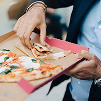 Midsection of businessman eating pizza from cardboard box in city
